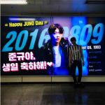 MYNAME ジュンQ、ファンからのお祝い看板の前で「ありがとう」